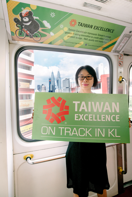 吉隆坡台湾贸易中心主任萧春雁特地登上电车宣传,双峰塔隐约可见。