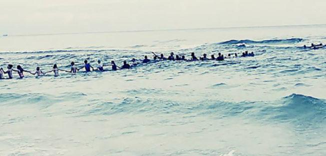 佛州巴拿马城海滩80名泳客为抢救被卷入急流的一家九口,筑起一堵人链墙,并成功将他们救回。 (网路图片)